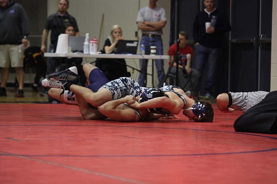 Senior+Austin+Crocker+pins+his+opponent+to+win+his+match.