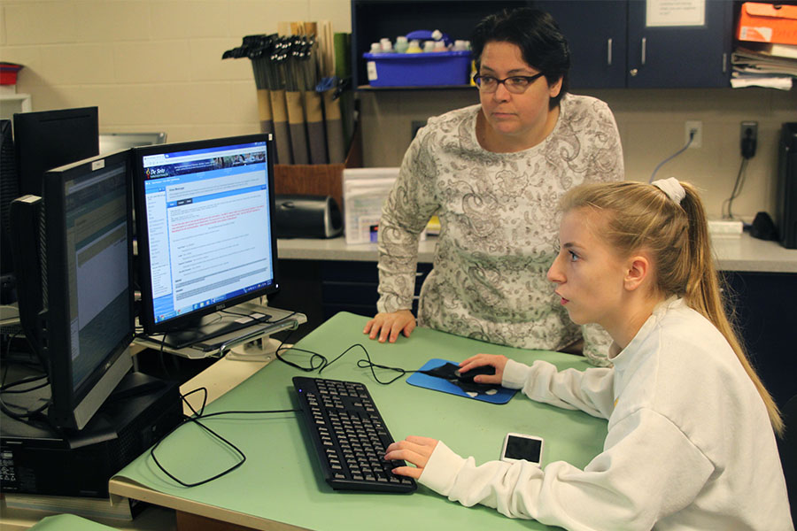 After completing the Rube Goldberg unit, engineering teacher Helga Brown helps junior Natalie Kalma submit a report.