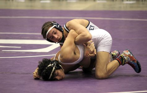 Concentrating during his match, senior Dylan Gowin holds down his opponent.