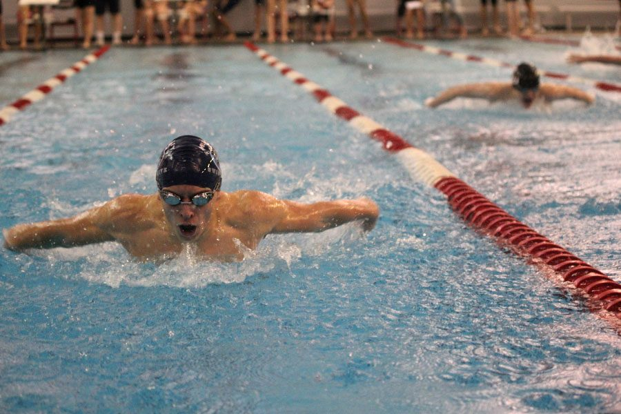 Lifting+himself+out+of+the+water%2C+sophomore+Carter+Lawson+competes+in+the+100+butterfly+at+Lansing+on+Tuesday%2C+Jan.+31.