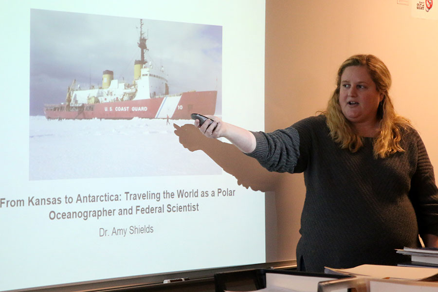 Gesturing towards the board, Dr. Amy Shields uses a powerpoint as an aid to speak to the Marine Biology club about her time in Antartica on Wednesday, February 8.