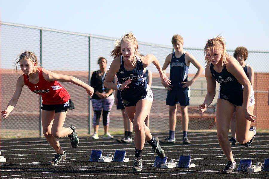 During the 100 meter dash, freshmen Khloe Knernschield (middle) and Megan Walkup (right) push off of their blocks at Blue Valley West on Thursday, March 23.