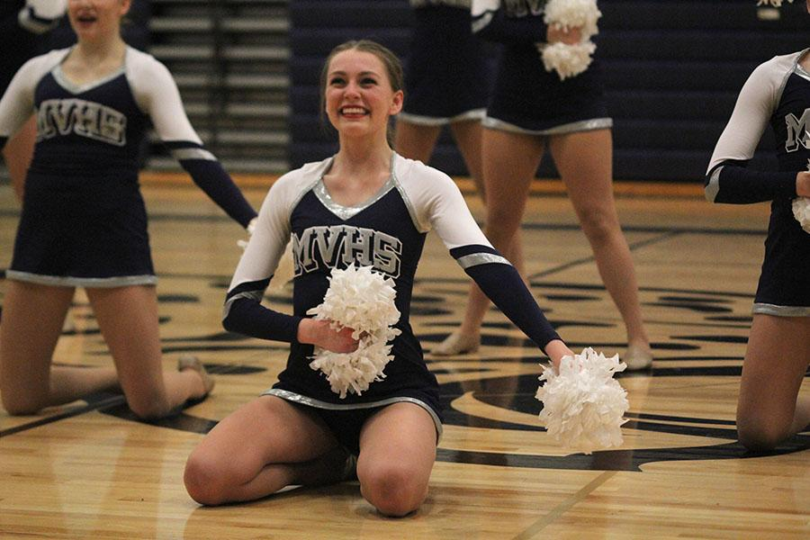 Senior+Julia+Kemp+smiles+during+the+pom+routine.