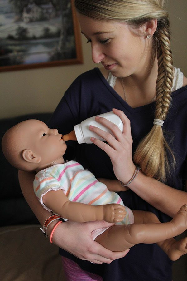 """Feeding the baby in her arms, senior Sarah Butler works on her Human Growth and Development project at home on Sunday, Feb. 5. """"I learned that babies are a lot more work than you'd think,"""" Butler said. """"If it started crying, I would have to drop everything to take care of it; it was so unpredictable."""""""