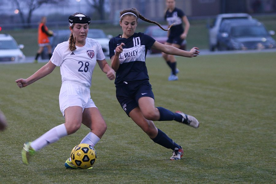 Pushing her opponent, junior Payge Bush battles for the ball during the game against Olathe North on Wednesday, March 29.