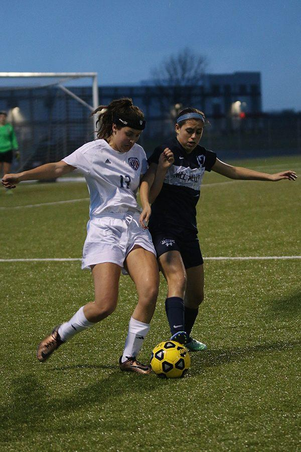 Junior Kylee Melendez reaches out with her foot to take the ball from another player.