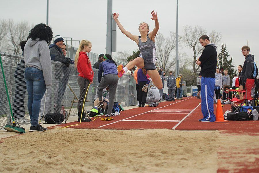 With her arms in the air, senior Morgan Thomas jumps as far as possible into the sandpit.