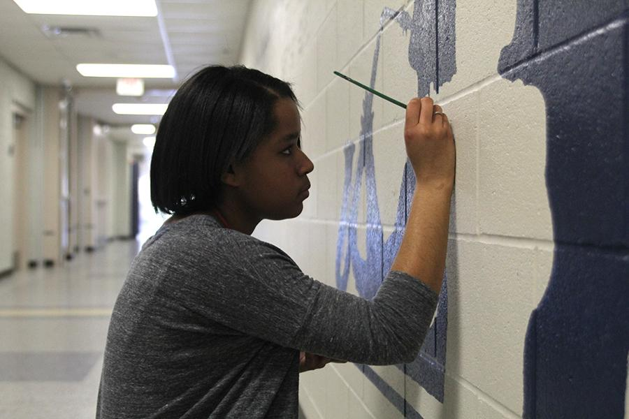 Working on the band mural, senior Jayna Smith helps paint the lower C-hallway for NAHS on Thursday, March 23.