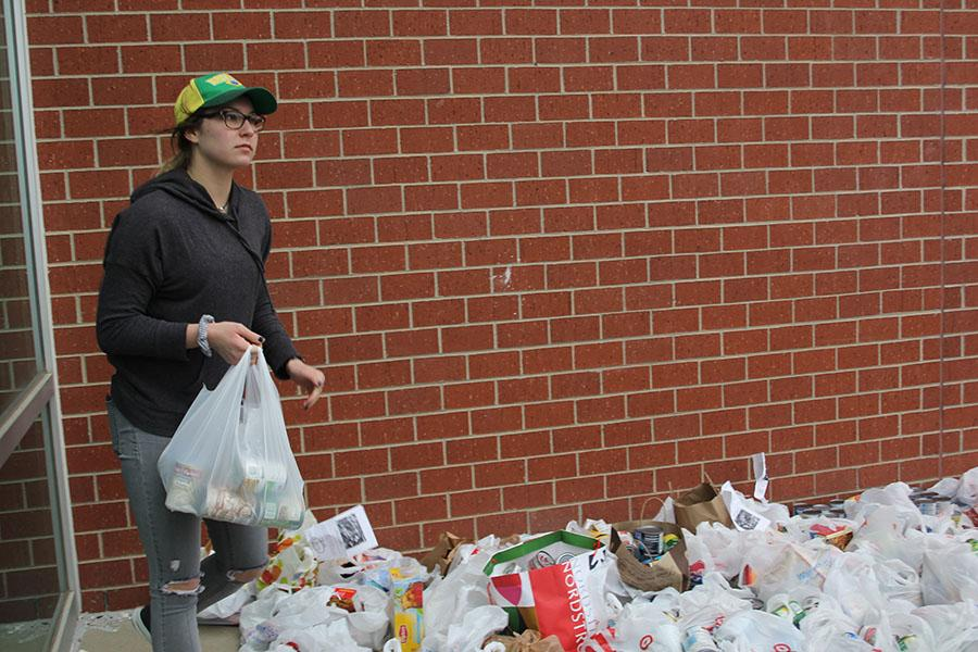 Organizing donated food, senior Emma Mantel participates in the NHS food drive on Sunday, Mar. 5.