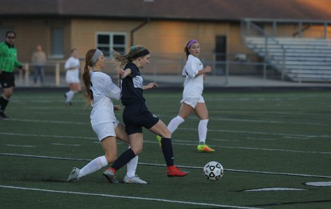 Fending off a Blue Valley player, freshman Emerson Kaiser dribbles the ball.