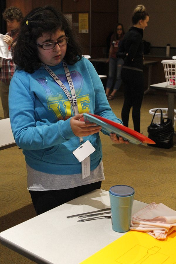 Freshman Alyssa Frias picks up plates to put them in the correct position while competing in the table setting event.