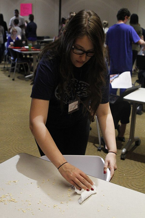 Junior Emily Wagner cleans off a table during the setting/bussing event.