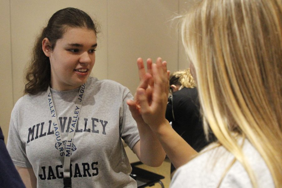 Junior Abby DeBrabander gives senior Sidney Lawyer a high five after competing in sorting silverware.