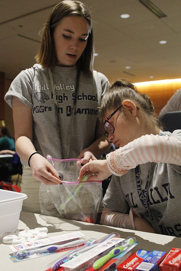 Junior Dakota Wilson assists sophomore Corinne Brown in the bag stuffing event.