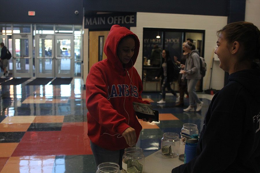 Junior Camryn Coleman donates to the NHS coin drive.