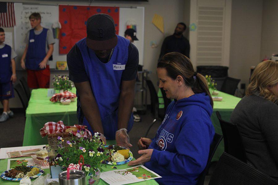 Junior Malik Redmond serves physical education teacher Amy McClure her food.