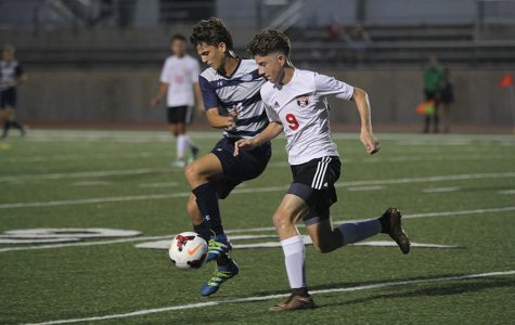 Fighting for the ball, senior Adam Grube blocks a Shawnee Mission North player on Tuesday, Aug. 30. The Jaguars won after the game was called at halftime due to inclimate weather, making the final score 4-0.