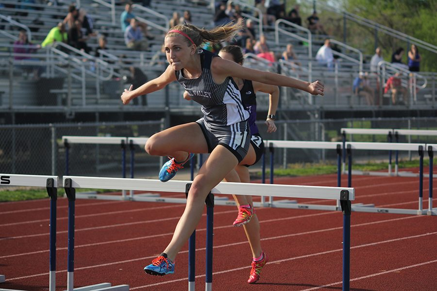 Freshman+Mallory+Scheelk+pulls+her+arms+back+as+she+clears+a+hurdle.