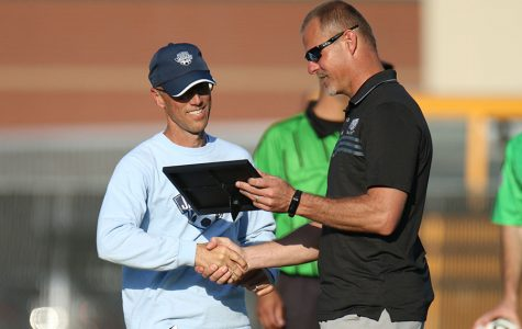 Before the girls soccer game on Tuesday, April 18, head coach Arlan Vomhof receives a plaque  honoring his 400th coaching victory from athletic director Jerald VanRheen.