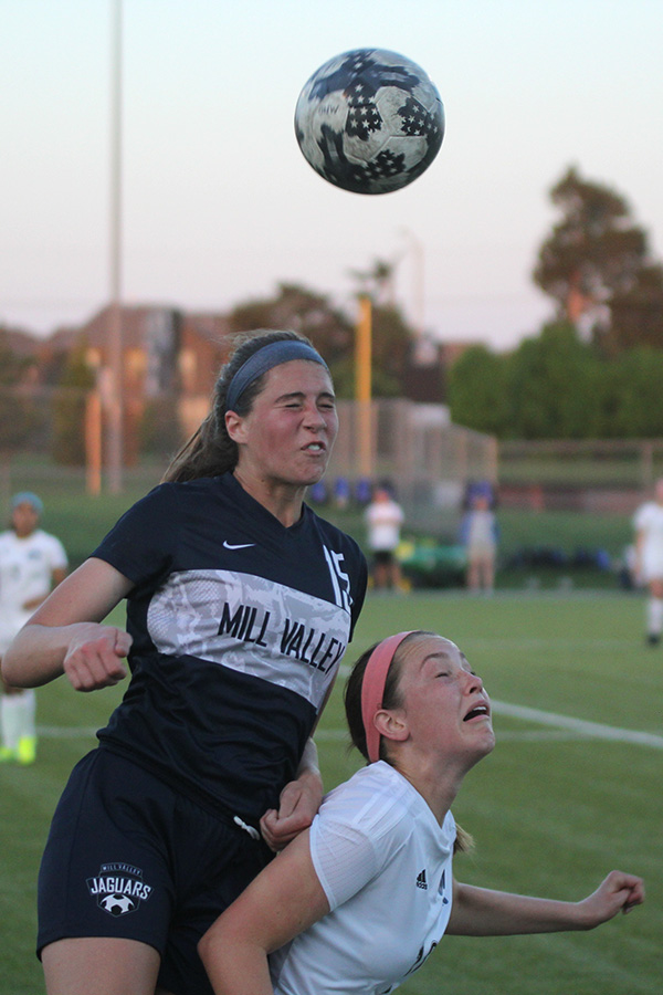 Jumping over her opponent, freshman Lanie Whitehill prepares to receive the ball using her head.