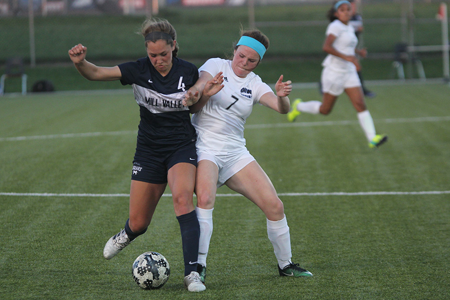 Freshman Ella Shurley fights with a player from Olathe Northwest for the ball.