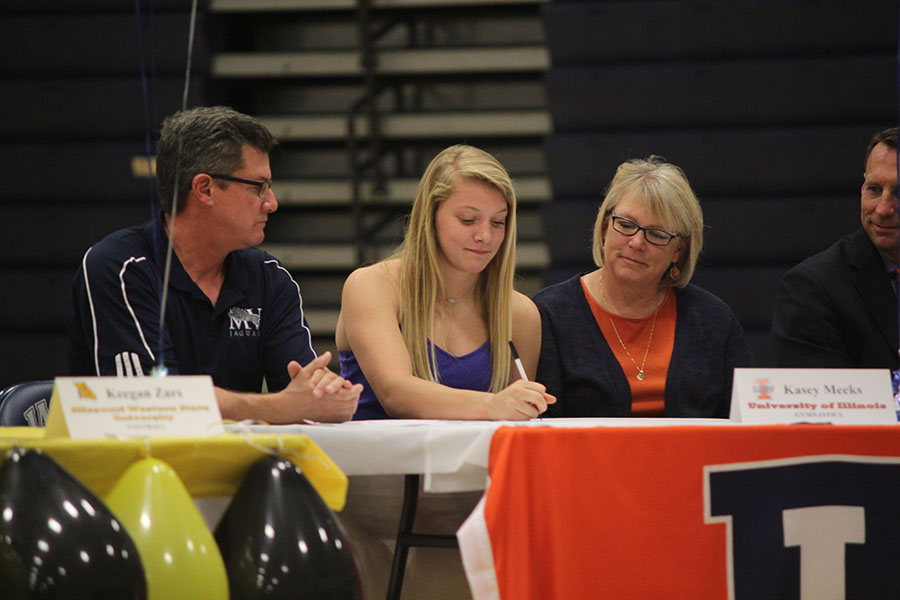 Signing her letter of intent to do gymnastics for the University of Illinois, senior Kasey Meeks smiles during the signing ceremony on May 2, 2017.