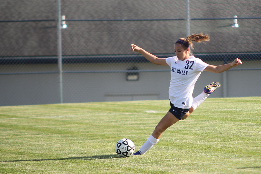 Sophomore Caroline Rutledge prepares to kick the ball to an open player.