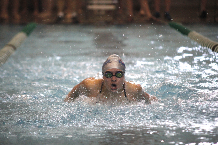 With+her+head+extending+from+the+water%2C+Junior+Jaz+Schwegman+competes+in+the+100+yard+butterfly.