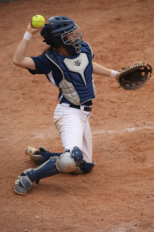 On+her+knees%2C+sophomore+Grace+Lovett+throws+the+ball+back+to+the+pitcher