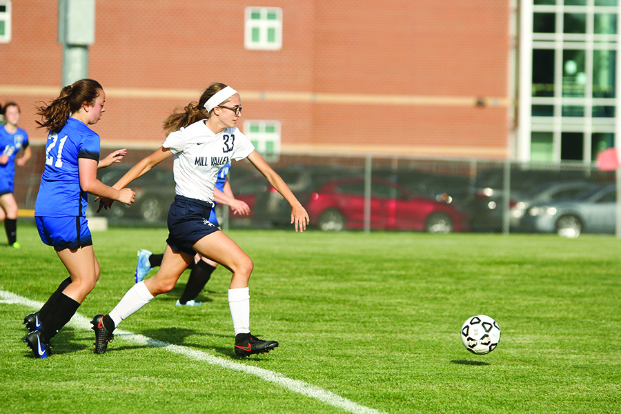 Sprinting past defenders and heading towards the goal, junior Erin Olson attempts to score.