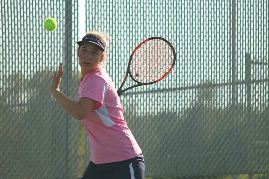 Following the ball with her eyes, senior Tori Wesp prepares to swing her racket on Tuesday, Sept. 19.