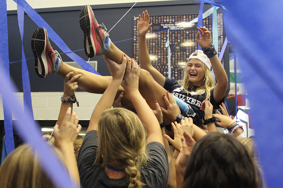 Holding up her arms, senior Bella Hadden crowd surfs during the blue bomb on Friday, September 8.