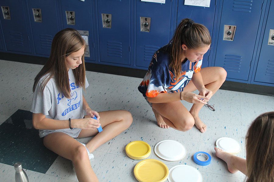Decorating+the+windows+of+their+locker+bank+on+Monday%2C+Sept.+4%2C+freshmen+Olivia+Boone+and+Katherine+Weigel+work+on+taping+yellow+plates.