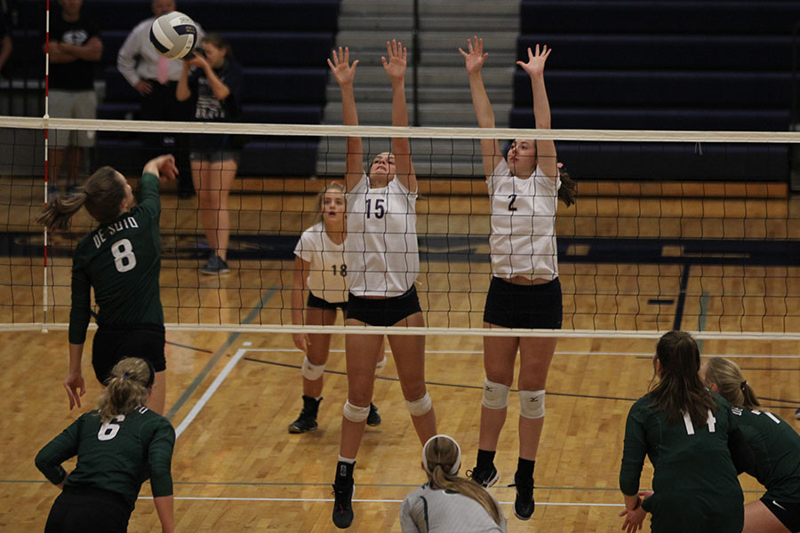 With+hands+in+the+air%2C+senior+Ava+Taton+and+freshman+Molly+Carr+attempt+to+block+the+ball+as+it+comes+over+the+net.