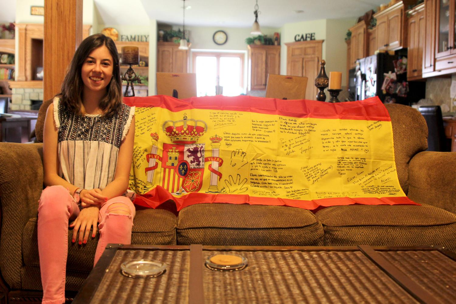 While in her host family's house, foreign exchange student and senior Elena Ortega Camazón poses in front of the Spanish flag signed by her family on Monday, Sept. 11.