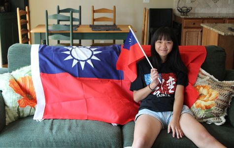 Sitting on the couch in her host family's home, foreign exchange student and senior Eunice Hsu poses in front of the Taiwanese flag while holding a flag on Monday, Sept. 4.