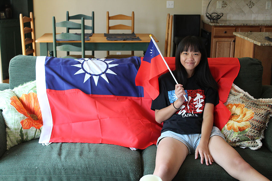Sitting+on+the+couch+in+her+host+family%27s+home%2C+foreign+exchange+student+and+senior+Eunice+Hsu+poses+in+front+of+the+Taiwanese+flag+while+holding+a+flag+on+Monday%2C+Sept.+4.