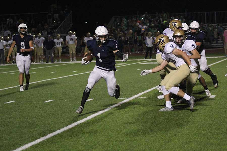 Avoiding members of the opposing team, junior running back Cameron Young runs downfield.