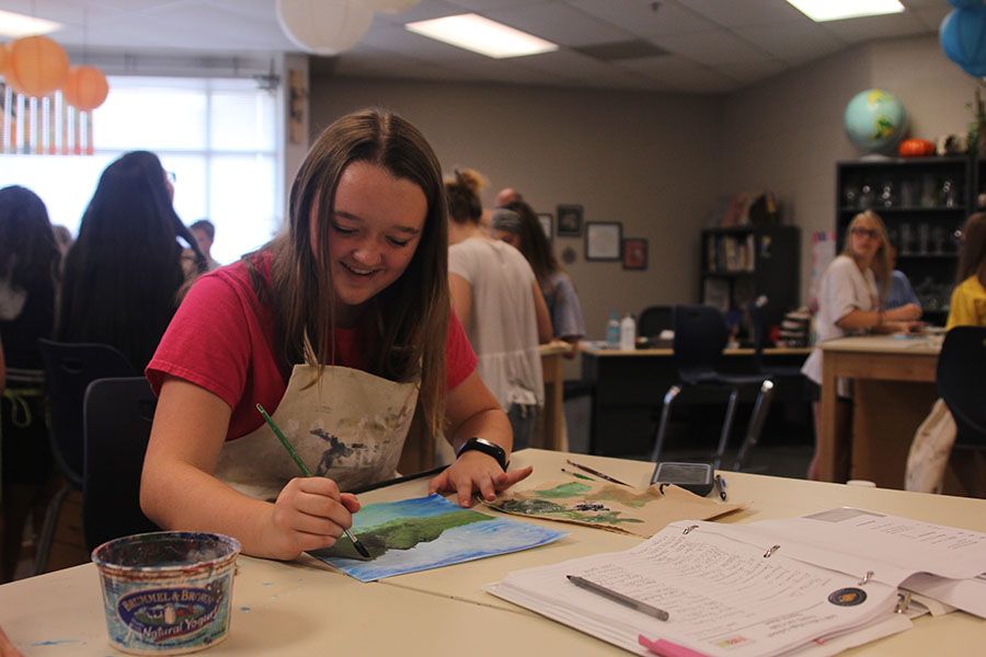 Freshman+Madison+Larson+smiles+as+she+finishes+her+version+of+painter+Bob+Ross%27+%22Mountain+View%22+on+Thursday%2C+Sept.+14.