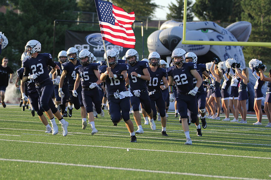 As+senior+Evan+Rice+is+holding+the+American+Flag%2C+the+football+teams+runs+out+onto+the+field+before+the+homecoming+game+on+Friday%2C+Sept.+9.