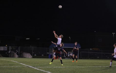 Junior Jake Ashford leaps over Topeka Seaman player to get the header on Monday, Oct. 2.
