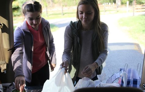 Participating in Trick-or-Treat-So-Others-Can-Eat on Monday Oct. 30, senior Hailey Stelle puts food into the trunk.
