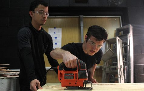 """Using the jigsaw, seniors Jayden Moore and Julian Velez focus on cutting out set pieces on Friday, Sept. 29. """"After you take the safety quiz,"""" Moore said. """"Everybody starts building and using jigsaws and screwdrivers."""""""
