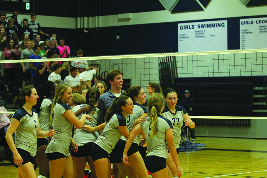 Looking at the scorboard on Thursday, Oct. 5, junior Joe Cosmillo celebrates with the varsity volleyball team after their win against Lansing.