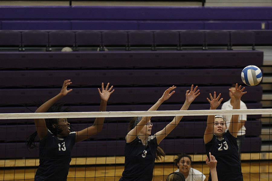 Freshman+Carlie+Bradshaw+attempts+to+block+the+ball+along+with+junior+Molly+Cosmillo+and+senior+Abby+Archibong.