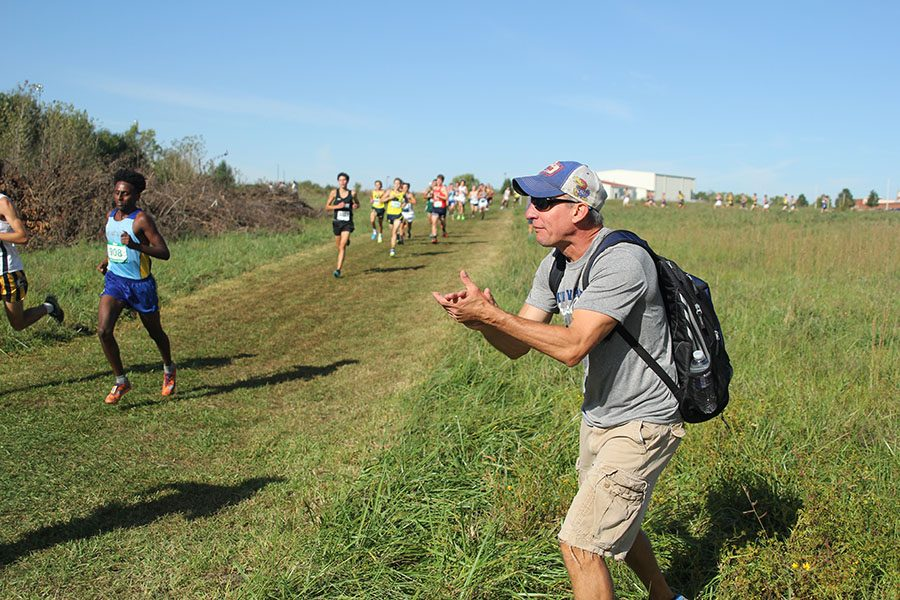 While on the course at Raymore-Peculiar High School, head coach Chris McAfee cheers on the varsity boy runners on Saturday, Sept. 30.