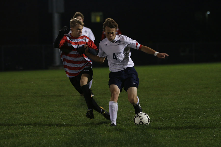 With the ball in his possession, senior Kyle Franklin attempts to push away the defender on Tuesday, Oct. 10. The team lost 3-4 to BVWest.