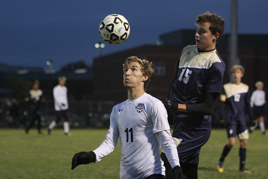 With+the+ball+coming+towards+his+head+junior+Jake+Ashford+looks+directly+to+block+it+from+an+Aquinas+player+during+the+sub-state+game+on+Tuesday+Oct.+31.