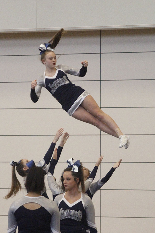 Practicing+her+stunt%2C+sophomore+Trinity+Ouellette+twists+as+she+falls+back+down+to+her+bases.