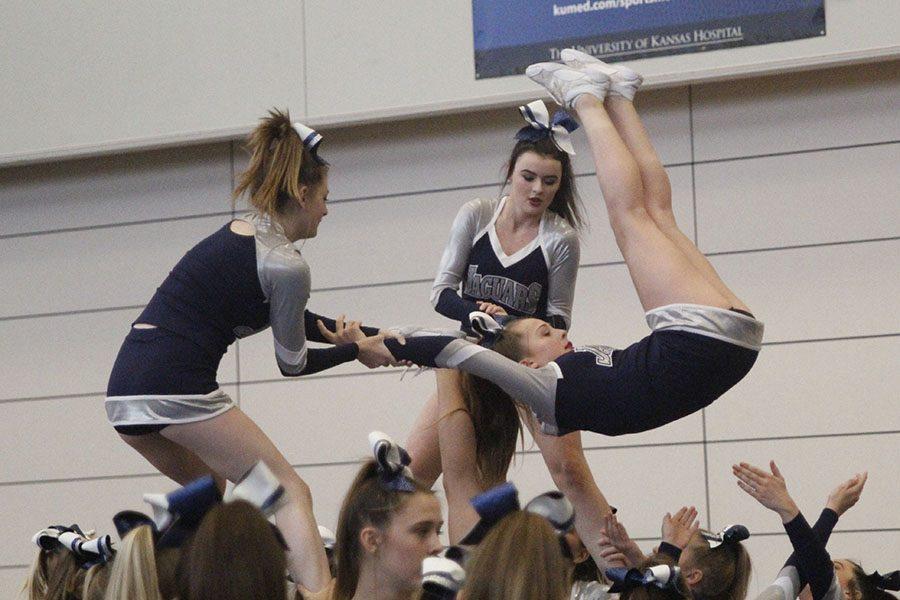 Perfecting+their+stunt%2C+seniors+Heather+Winne+and++Nataline+Cooper+flip+junior+Lexi+Knappen+over.